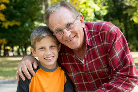 front facing: Portrait of senior man with arm around grandson in woods
