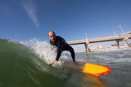 Mid adult man surfing on yellow surfboard next to bridge, Los Angeles, California, USA