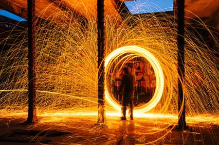 slow motion: Man creating circular golden spark light trails in derelict building