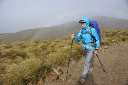 move in: Young female hiker in front of rainbow, Kepler Track, New Zealand