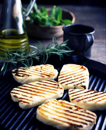 Still life of grilled haloumi cheese with rosemary on grill