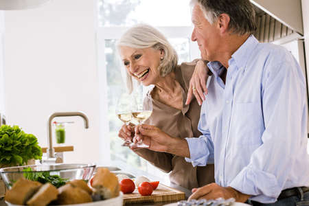 housing lot: Senior couple raising a glass of wine to each other in kitchen