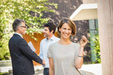 sold small: Estate agent and client shaking hands outside new house
