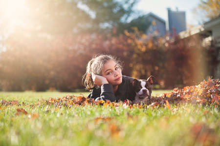 Girl with Boston terrier puppy lying on front on Autumn leaf covered grass, resting on elbow looking at camera