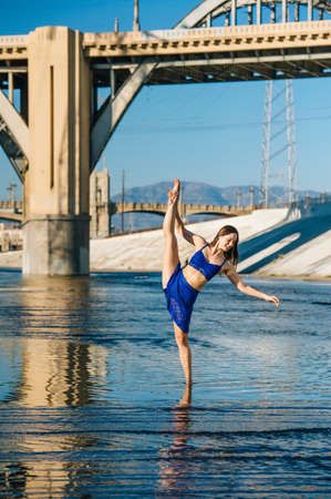Dancer ankle deep in water, leg raised, balancing on one leg, in front of bridge, Los Angeles, California, USA LANG_EVOIMAGES