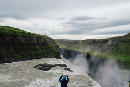 world at your fingertips: High angle rear view of mid adult woman using smartphone to photograph waterfall, Iceland LANG_EVOIMAGES