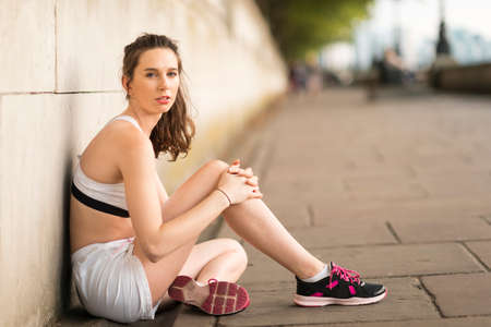 Portrait of young female runner sitting on riverside LANG_EVOIMAGES