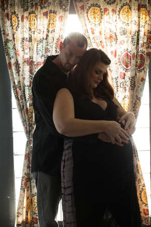 hopefulness: Mid adult man standing behind pregnant mid adult woman arms around, touching stomach