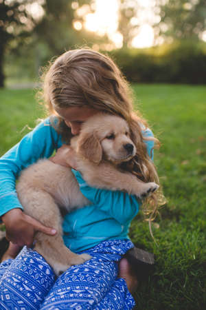 Girl hugging puppy in garden at sunset