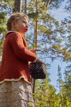 Girl dressed in retro clothing with basket in forest