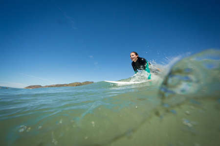Surface level view of young woman on surfboard in ocean, Ventura, USA