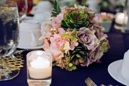 Prepared wedding reception table with flower arrangements and candlelight