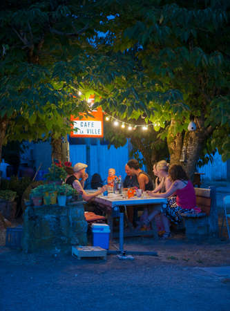30 years old man: Three generation family at cafe table at night, France