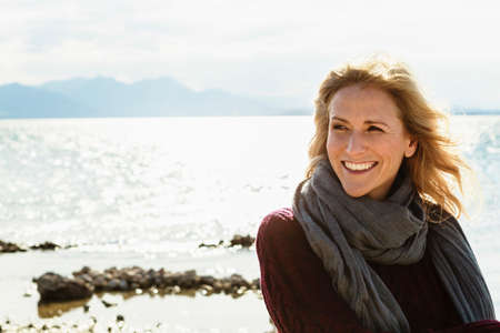 Portrait of mature woman beside lake, smiling