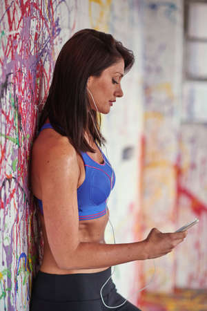 entertaining area: Woman wearing crop top leaning against warehouse graffiti wall choosing smartphone music