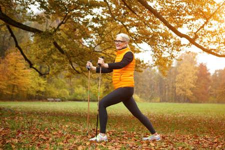 Senior female nordic walker exercising in park