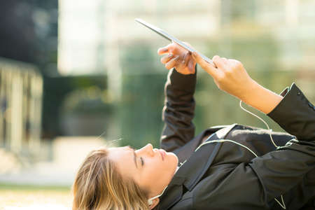 Young city businesswoman lying outside office reading digital tablet