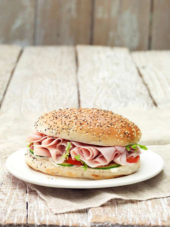 Wafer thin honey roast ham sandwich in seeded bun on plate LANG_EVOIMAGES