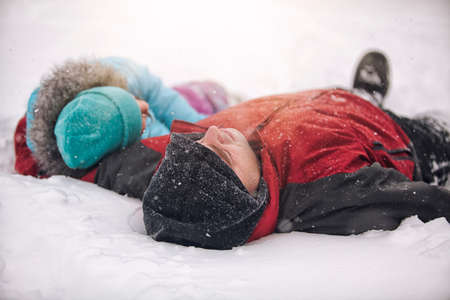Father and daughter wearing knit hats lying on backs in snow