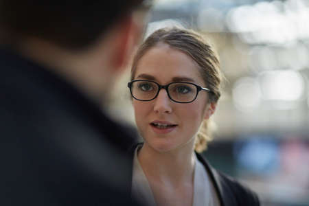 Young businesswoman wearing eye glasses talking to colleague LANG_EVOIMAGES