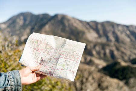 Young mans hand holding folding map, Chilao Campgrounds, Los Angeles, California, USA