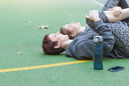Young women lying on sports court stretching legs, looking up smiling
