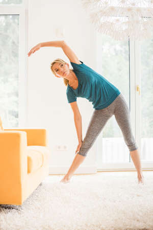 Mature woman bending over sideways whilst exercising in living room
