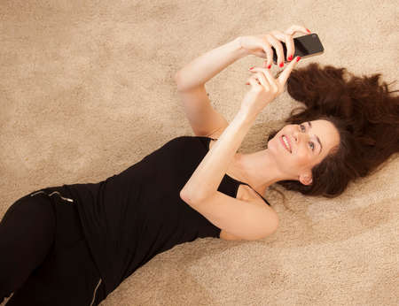 narcissist: High angle view of young woman lying on carpet using smartphone smiling LANG_EVOIMAGES