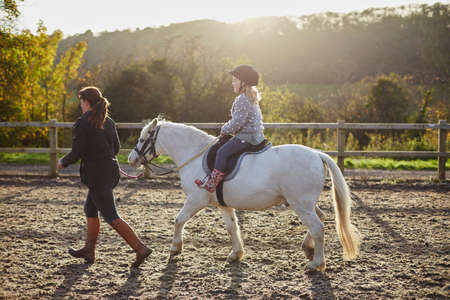 Instructor leading girl riding white pony in equestrian arena LANG_EVOIMAGES