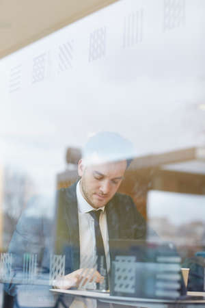 View through window of businessman sitting at table texting, looking down LANG_EVOIMAGES