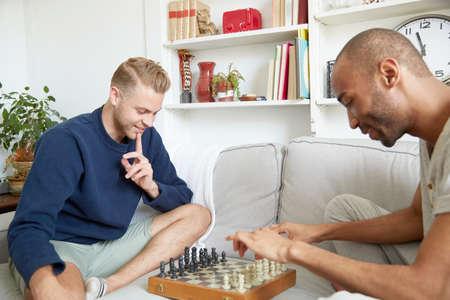 Men sitting on sofa playing chess smiling