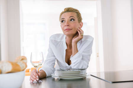 Mature woman daydreaming whilst drinking wine at kitchen counter