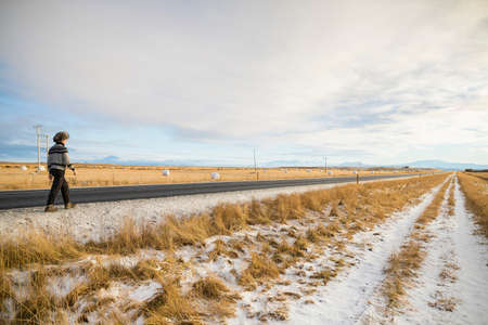 Woman walking along country road, Iceland LANG_EVOIMAGES