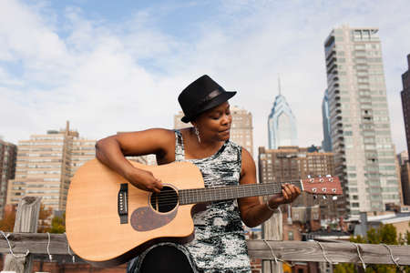 entertaining area: Mature woman playing guitar in front of Philadelphia skyline, USA
