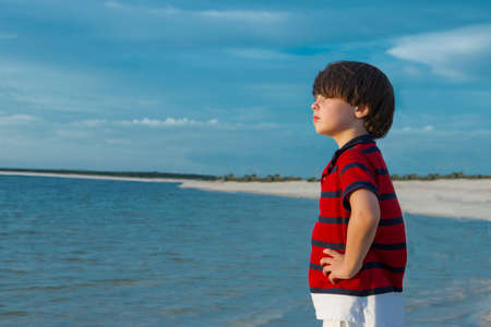 Young boy standing in sea, hands on hips, looking at view