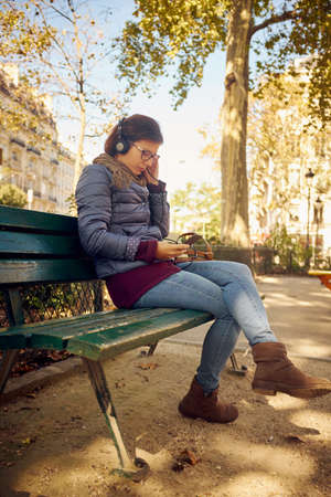 entertaining area: Mid adult woman sitting in park selecting smartphone music for headphones
