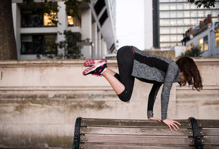 seating area: Young woman jumping over park bench in city LANG_EVOIMAGES
