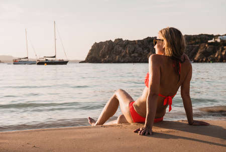 Mid adult woman sitting looking out from beach, Menorca, Balearic islands, Spain LANG_EVOIMAGES