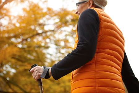 Low angle view of senior female nordic walker in autumn park