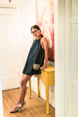 passageways: Portrait of young woman wearing mini dress leaning against hallway table