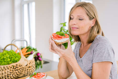 Mature woman eating open sandwich in kitchen LANG_EVOIMAGES
