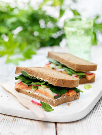 Chopping board with british ultimate sandwich, salmon, spring onions, radishes in brown bread on garden table