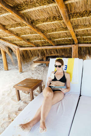 Mid adult woman relaxing on sun lounger, under cabana, Tulum, Riviera Maya, Mexico