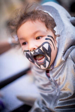 Angled view of girl dressed as shark, teeth painted on face, mouth open looking away LANG_EVOIMAGES