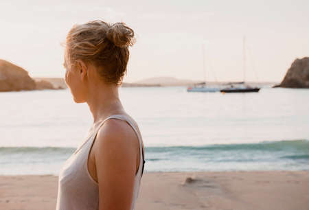 Mid adult woman looking out from beach, Menorca, Balearic islands, Spain