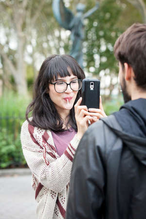 Over shoulder view of young woman photographing boyfriend on smartphone in park
