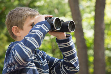 finding out: Boy looking through binoculars in woods LANG_EVOIMAGES