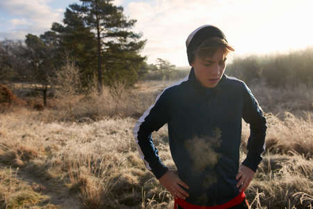 athletic wear: Teenage boy on frosty grassland, visible breath, hands on hips looking down