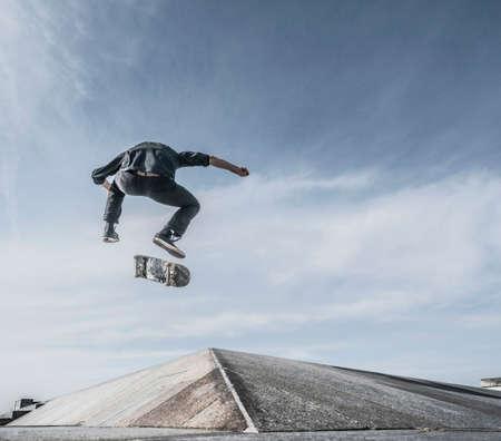 low self esteem: Young man skateboarding on roof LANG_EVOIMAGES