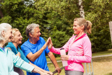 Group of adults taking a break from exercise, outdoors, smiling